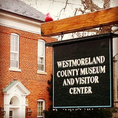 Westmoreland County Museum, Library and Visitor Center sign with icicles.  View of the historic courthouse behind.