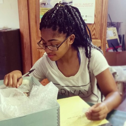 Tamysinae Brown looking through a box of artifacts in Westmoreland County Museum