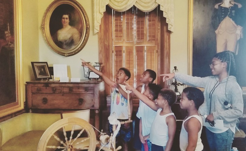 Tamysinae giving a tour at the museum to her family.   They are pointing at the museum's portrait of George Washington.